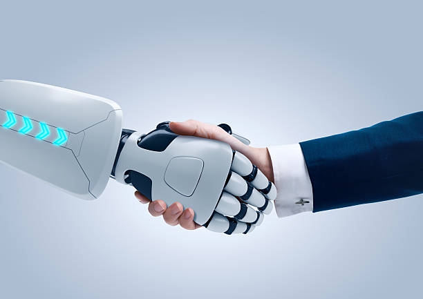 White mechanical robot hand shaking hands with a human hand